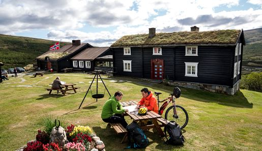 Cyclists planning their trip at a table outside Grimsdalshytta Lodge in Norway