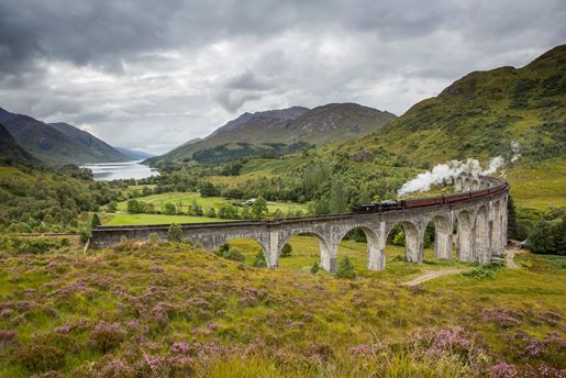 View down the valley of a train going over the Glenfinnan Viaduct in The Highlands in Scotland