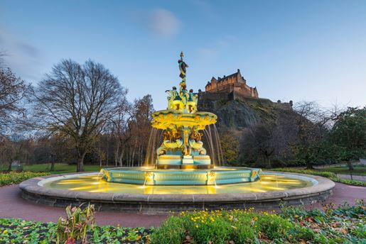 The Ross Fountain and Edinburgh Castle from Princes Street Gardens at dusk in Scotland's capital city