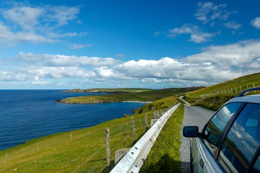 Car driving along the B9122 overlooking the sea near Scousburgh on Mainland in Shetland, Scotland