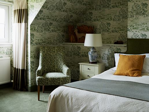 Green wallpaper and suite bed in a room at the Kinloch Lodge in the Scottish Highlands