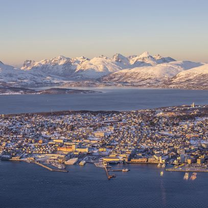 Birds-eye view of the beautiful cityscape with the dramatic mountain range behind in Tromsø in Norway.