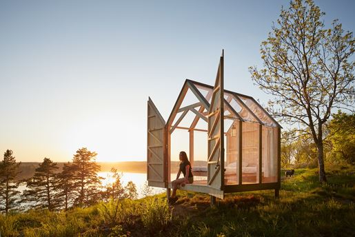 A glass cabin perched on the water's edge in Southwest Sweden during summer