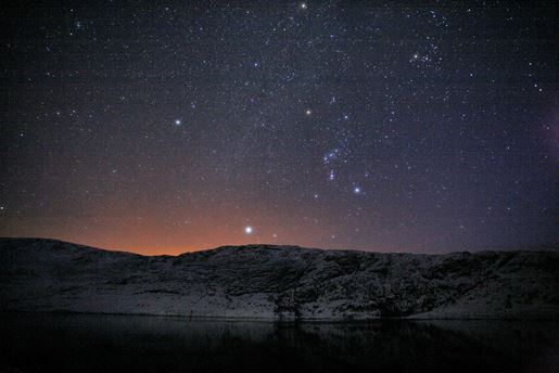 A clear starlit night over Loch Cluanie in the northwest Highlands of Scotland
