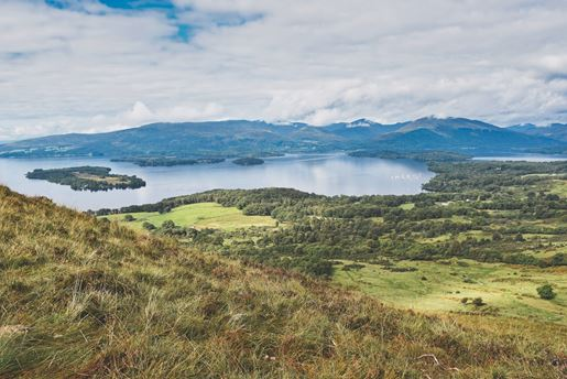 View from a grassy hillside over Loch Lomond and Trossachs National Park on a clear day in the Scottish Lowlands