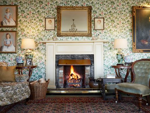 The ornate fireplace and wallpaper in the drawing room of the Kinloch Lodge in the Scottish Highlands